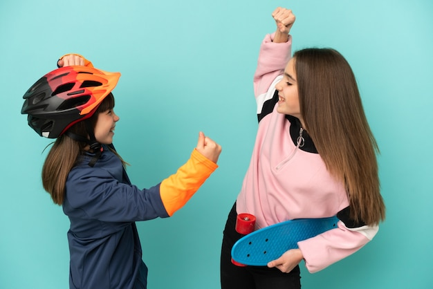 Małe siostry ćwiczące jazdę na rowerze i łyżwiarki na białym tle świętują zwycięstwo w pozycji zwycięzcy