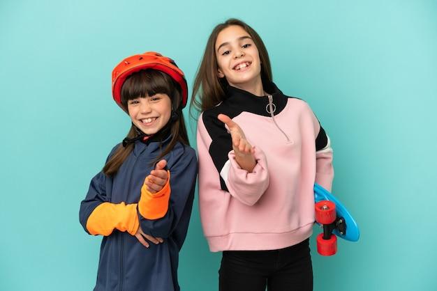 Małe siostry ćwiczące jazdę na rowerze i łyżwiarstwo na białym tle na niebieskim tle, ściskając ręce, aby zamknąć dobrą ofertę