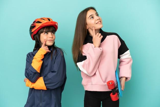 Małe siostry ćwiczące jazdę na rowerze i łyżwiarstwo samodzielnie myśląc o pomyśle, patrząc w górę