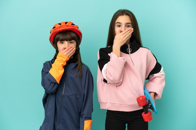 Małe siostry ćwiczące jazdę na rowerze i łyżwiarz na białym tle zakrywają usta rękami za powiedzenie czegoś niewłaściwego