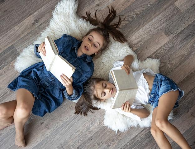 Małe siostry dziewczynki czytają książki leżące na podłodze, widok z góry.