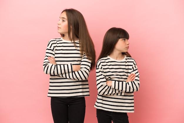 Małe siostry dziewczynki izolowane z mylącym wyrazem twarzy podczas gryzienia warg