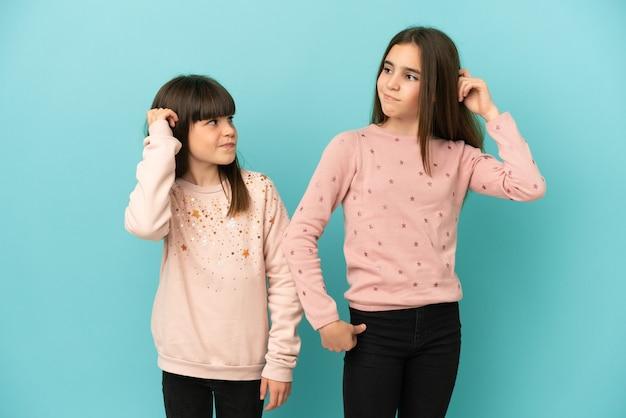 Małe siostry dziewczynki na białym tle na niebieskim tle, które mają wątpliwości podczas drapania się po głowie