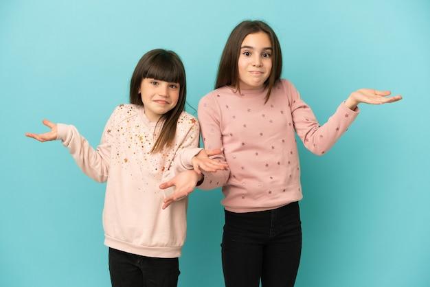 Małe siostry dziewczynki na białym tle na niebieskim tle mają wątpliwości podczas podnoszenia rąk i ramion