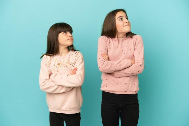 Małe siostry dziewczynki na białym tle na niebieskim tle robiące gest wątpliwości podczas podnoszenia ramion