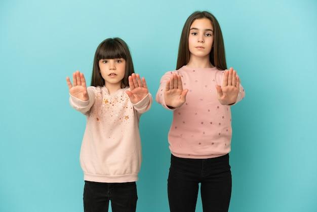 Małe siostry dziewczynki na białym tle na niebieskim tle robiące gest zatrzymania dla rozczarowanych opinią