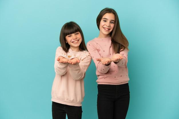 Małe siostry dziewczynki na białym tle na niebieskim tle trzymające wyimaginowaną copyspace na dłoni, aby wstawić reklamę