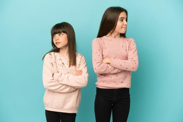 Małe siostry dziewczynki na białym tle na niebieskim tle z mylącym wyrazem twarzy podczas gryzienia warg
