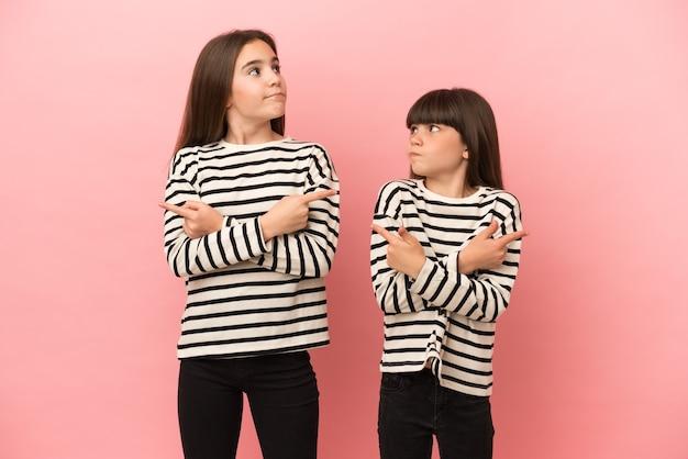 Małe siostry dziewczynki na białym tle na różowym tle wskazujące na boki mające wątpliwości