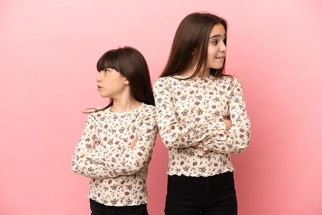 Małe siostry dziewczynki na białym tle na różowym tle z mylącym wyrazem twarzy podczas gryzienia wargi