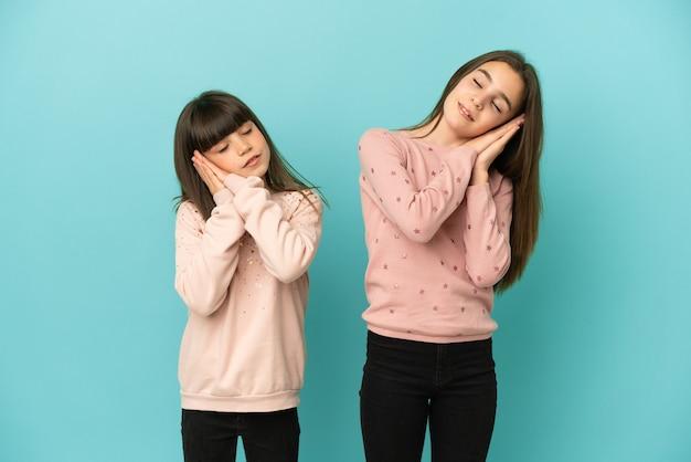 Małe siostry dziewczynki na białym tle robią gest snu w uroczym wyrazie