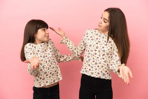 Małe siostry dziewczynki odizolowały się, wykonując nieważny gest podczas podnoszenia ramion