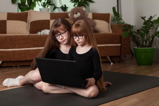 Małe siostry dziewczynki prowadzą lekcję gimnastyki online w domu