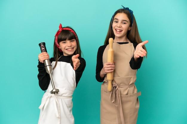 Małe siostry gotują w domu na białym tle na niebieskim tle, ściskając ręce, aby zamknąć dobrą ofertę