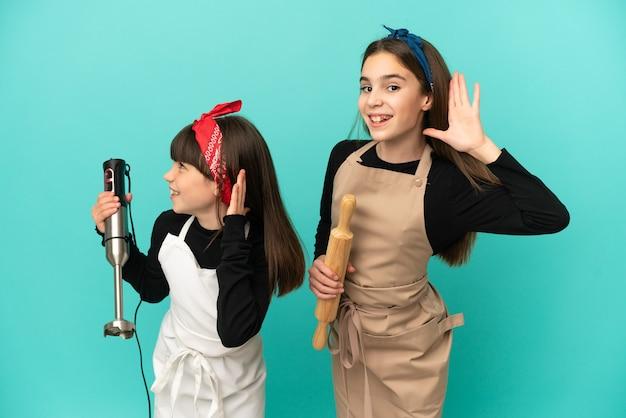 Małe siostry gotujące w domu na białym tle, słuchając czegoś, kładąc rękę za ucho