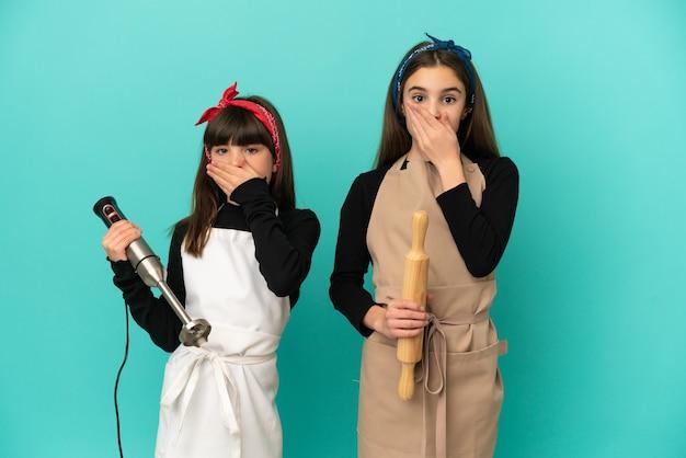 Małe siostry gotujące w domu na białym tle zakrywające usta rękami za powiedzenie czegoś niewłaściwego