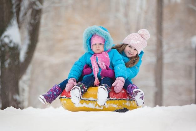 Małe siostry jeżdżą śnieżną rurką ze wzgórza zimą