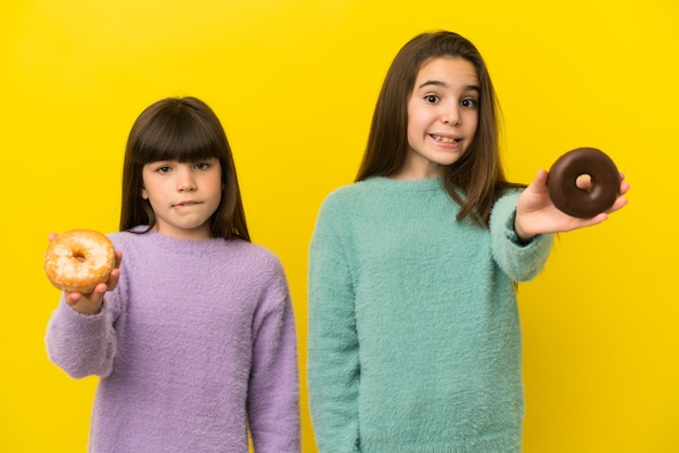Małe siostry na żółtym tle trzymające pączka i smutne