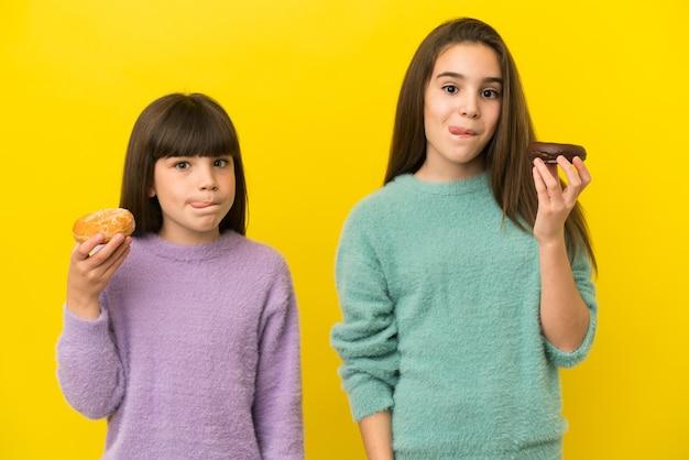 Małe siostry na żółtym tle trzymające pączka
