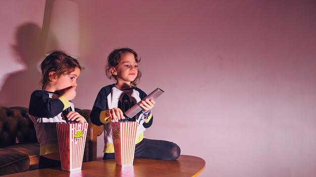 Małe siostry oglądające telewizję w ciemności