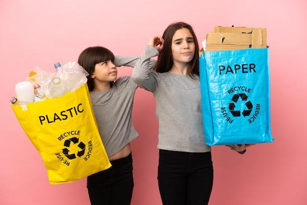 Małe siostry przetwarzają papier i plastik na białym tle na różowym tle, mając wątpliwości podczas drapania się po głowie