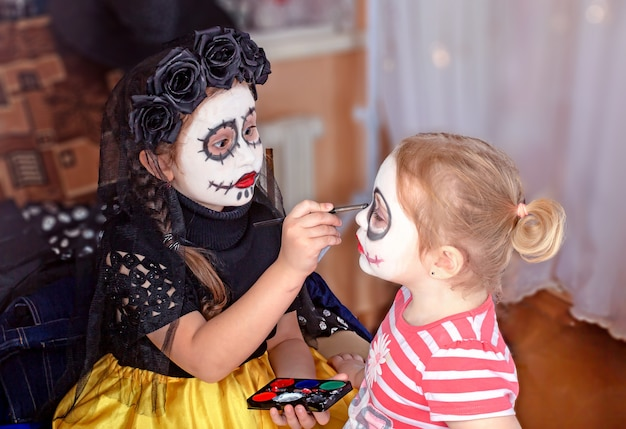 Małe siostry robią makijaż hallowen