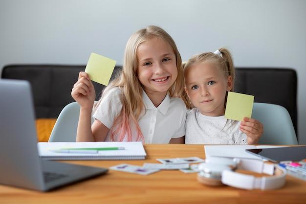 Małe siostry robią razem szkołę online w domu