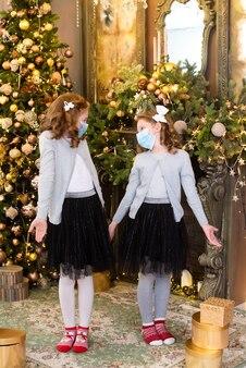 Małe siostry są zaskoczone. w pobliżu choinki stoją rudowłose dziewczyny w maseczkach medycznych. smutne, wakacje są zepsute. prezenty, girlandy nie są zachęcające