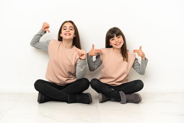 Małe siostry siedzące na podłodze na białym tle dumne i zadowolone w miłości do siebie koncepcji