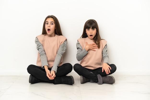 Małe siostry siedzące na podłodze na białym tle ze zdziwieniem i zszokowanym wyrazem twarzy