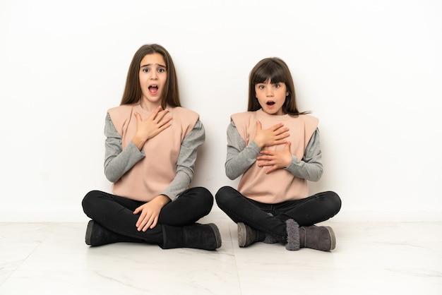 Małe siostry siedzące na podłodze na białym tle