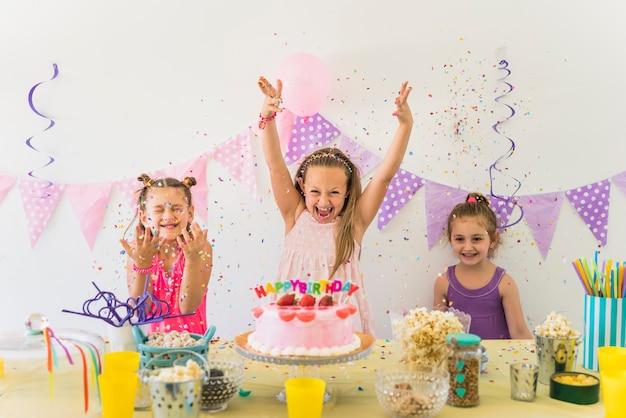 Małe śliczne dziewczyny ma zabawę podczas gdy świętujący przyjęcia urodzinowego