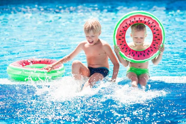 Małe słodkie dzieci w pobliżu basenu. dzieci bawią się latem.