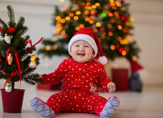 Małe słodkie dziecko w czerwonym body i czapce boże narodzenie siedzi na podłodze z małą choinką
