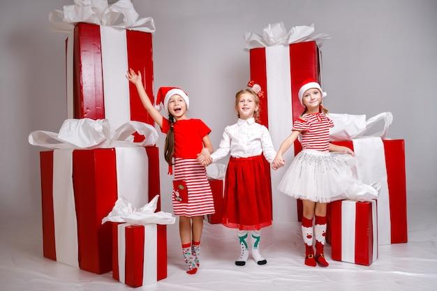 Małe słodkie dziewczyny w studio z dekoracją zimowych wakacji i rekwizytami.