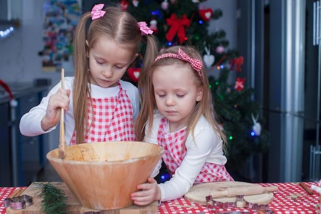 Małe słodkie siostry pieczą piernikowe ciasteczka na boże narodzenie