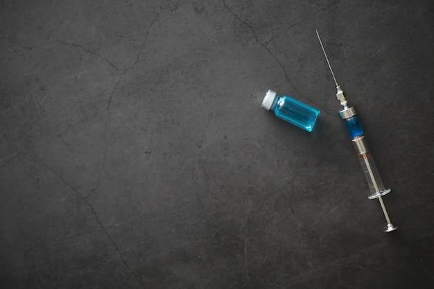 Małe słoiki z wtryskiem i strzykawką do wstrzykiwań na niebieskim tle w pobliżu wzoru chemicznego