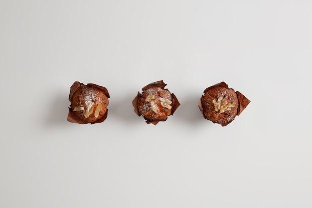 Małe smaczne słodkie babeczki posypane cukrem pudrem na białym tle na białej powierzchni. deser do picia herbaty. wyśmienite wyroby cukiernicze wypiekane przez cukiernika. koncepcja fast foodów i żywienia