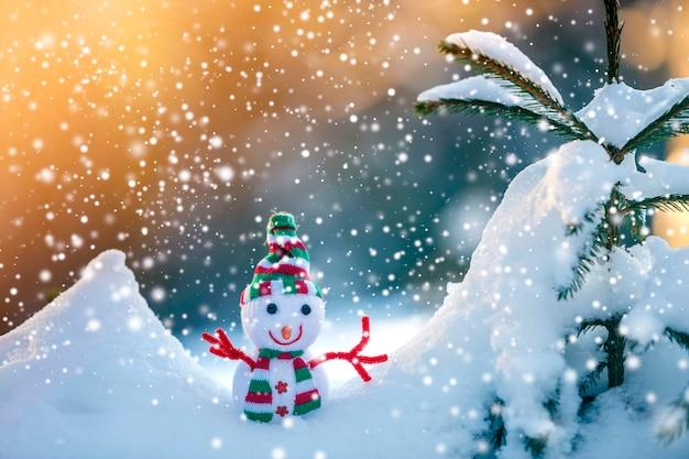 Małe śmieszne zabawki bałwan dziecko w dzianiny kapelusz i szalik w głębokim śniegu na zewnątrz na jasny niebieski i biały kopii przestrzeni tle. kartkę z życzeniami szczęśliwego nowego roku i wesołych świąt.