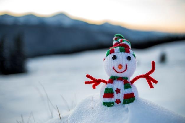 Małe śmieszne zabawki dziecko bałwan w dzianiny kapelusz i szalik w głębokim śniegu odkryty na niewyraźne pokryte śniegiem góry krajobraz tło. szczęśliwego nowego roku i wesołych świąt z życzeniami motywu.