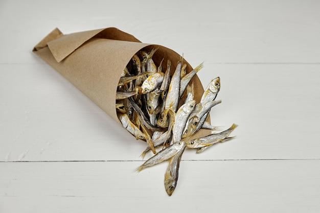 Małe solone suszone ryby w papierowej torbie na białym stole