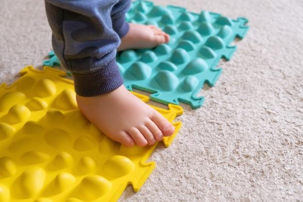 Małe stopy dziecka na prążkowanym dywanie.