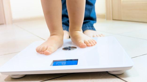 Małe stopy dziecka stojącego na podłodze cyfrowej wagi w domu.