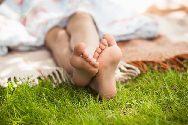 Małe stopy dziewczynki leżące na trawie w słoneczny dzień