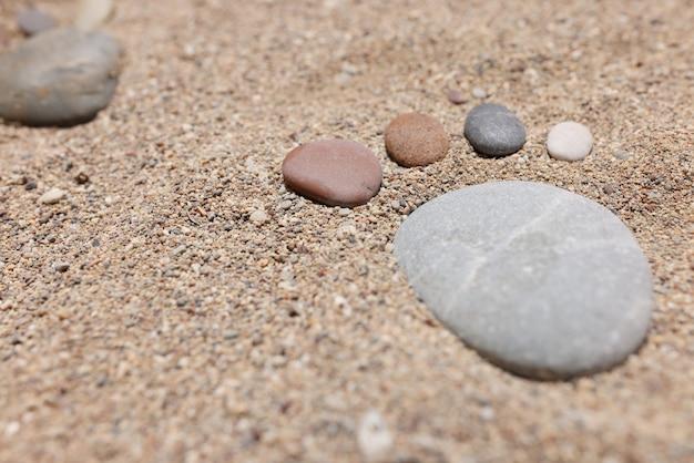 Małe stopy są ułożone z kamieni na piecu na zbliżenie plaży morskiej