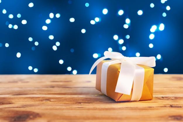Małe świąteczne pudełka na prezenty na drewnianym stole na tle światła bokeh