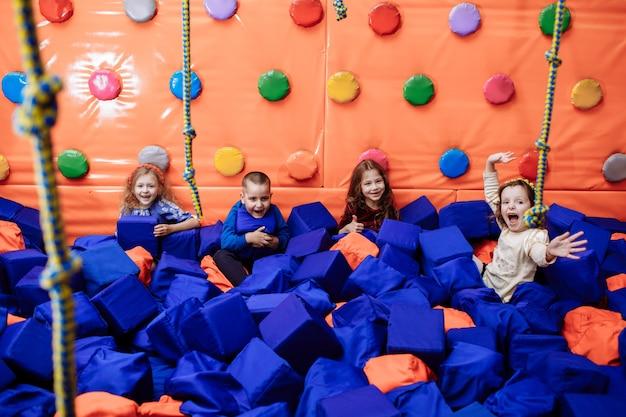 Małe szczęśliwe dzieci bawią się i bawią w suchym basenie z kostkami paralon w centrum rozrywki dla dzieci