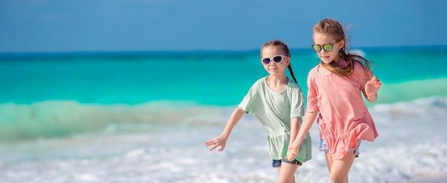 Małe szczęśliwe dzieci świetnie się bawią na tropikalnej plaży, grając razem. urocze dziewczyny tanczy na karaibskiej wyspie