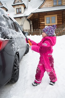 Małe szczęśliwe dzieci zimą mroźny poranek czyszczą samochód ze śniegu