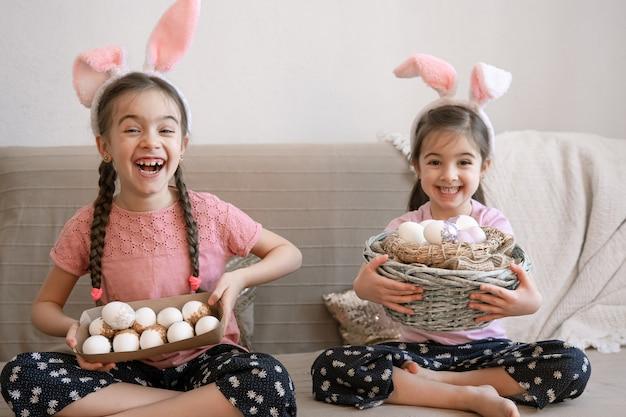 Małe szczęśliwe siostry z uszami królika, z pisankami. koncepcja wakacji wielkanocnych.
